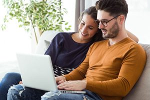 young-couple-using-laptop-on-the-sofa-at-home