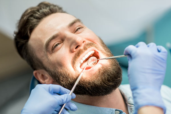 Man-during-teeth-examination-at-the-dental-office