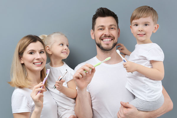 Young-family-brushing-teeth-on-grey-background