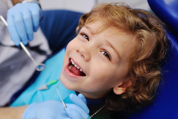 smiling-child-sitting-in-a-blue-chair-dental